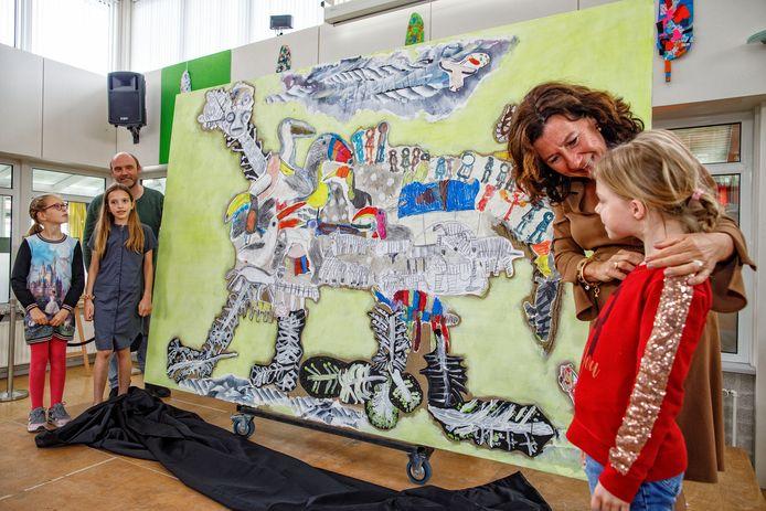 Het kunstwerk van Reinout van Vught (links) is net onthuld door kinderen van het onderwijscentrum Leijpark. De wethouder complimenteert leerling Joanna (rechts) met haar bijdrage.