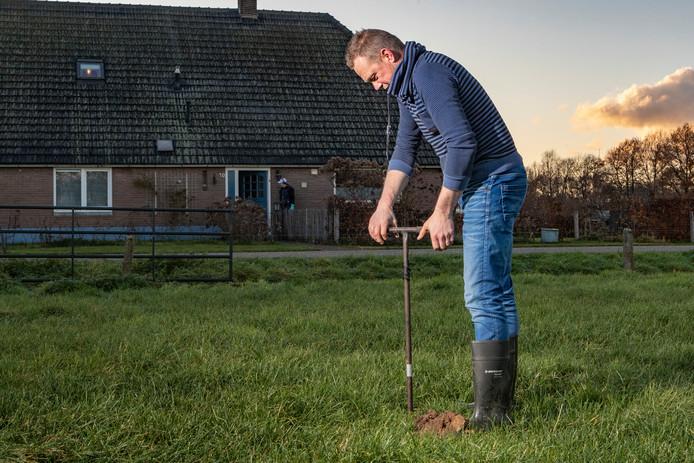 Geert Stevens uit Holten bekijkt met een boor het grondwaterpeil.