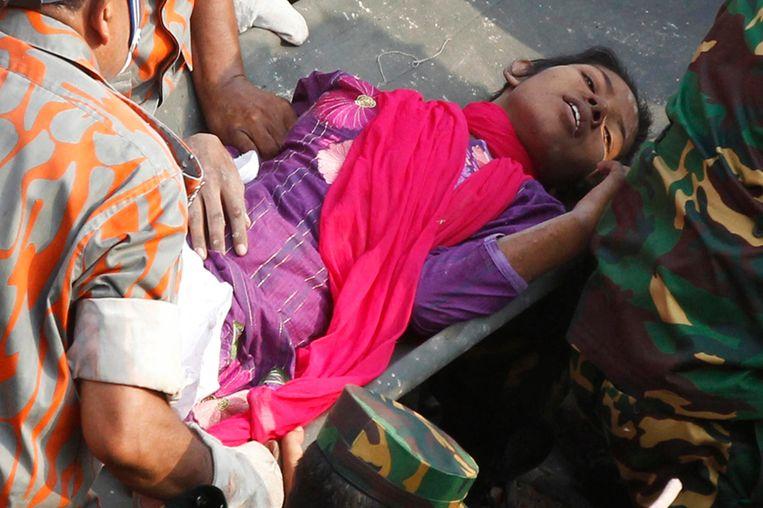 De vrouw die zeventien dagen onder het puin overleefde, wordt naar een ambulance afgevoerd. Beeld reuters