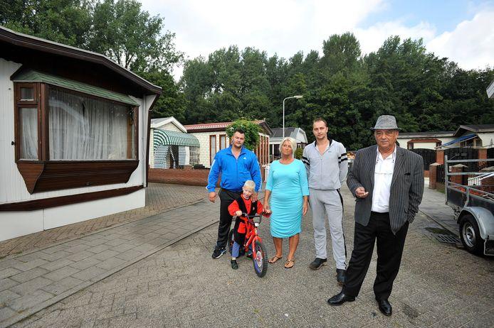 Een deel van de familie Brink op 'hun' woonwagencentrum in Arnhem. Rechts Nino Halberstadt van Vereniging Sinti, Roma en Woonwagenbewoners Nederland. Tweede van rechts Lammert Brink.