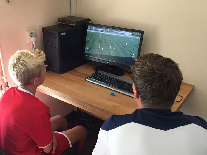 Een voetballer van Alphense Boys bekijkt met zijn trainer naar beelden.