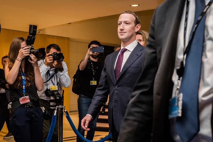 Zuckerberg door een woud van fotografen en cameramensen in Brussel.