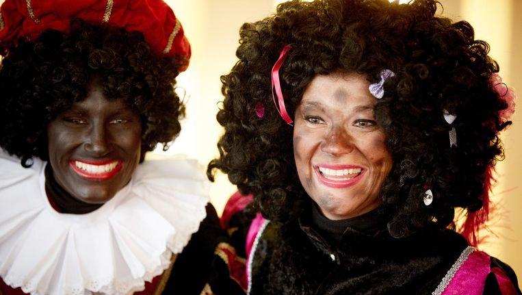 Een Zwarte Piet en een Piet met roetvegen uit het gevolg van Sinterklaas. Beeld anp