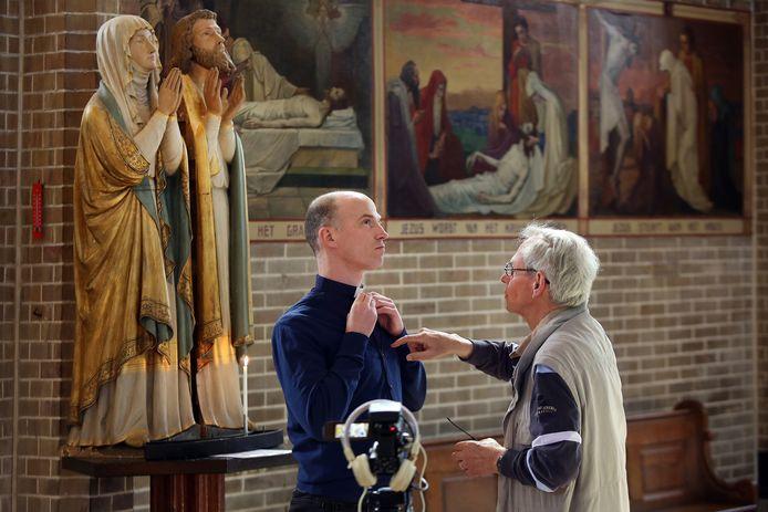 In de Heilige Laurentiuskerk in 't Ginneken worden voor Goede Vrijdag kruisweg-meditaties opgenomen. Pastoor Lars Peetam (links) krijgt een microfoontje op van cameraman en parochiebestuurslid Henk Bakker.