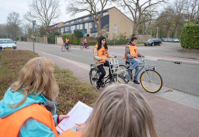 Twee deelnemers aan het praktijkdeel van het verkeersexamen in Wageningen passeren twee ouders die aan de Churchillweg toekijken of alles verloopt volgens de regels van de verkeerswetten.
