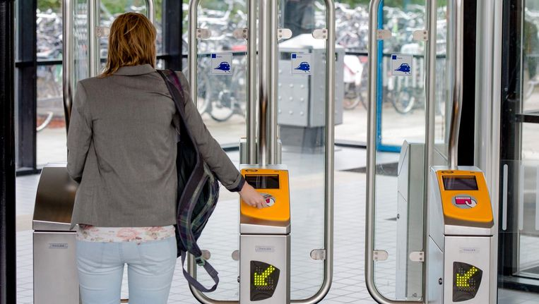 Een reiziger bij een toegangspoortje op het station. Beeld anp
