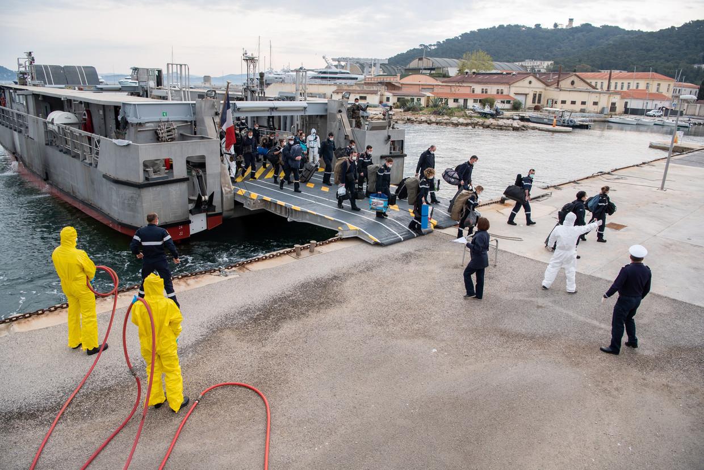 Een deel van de bemanning van het Franse vliegdekschip Charles de Gaulle wordt aan land gebracht in Saint-Mandrier-sur-Mer, nabij Toulon. Beeld EPA