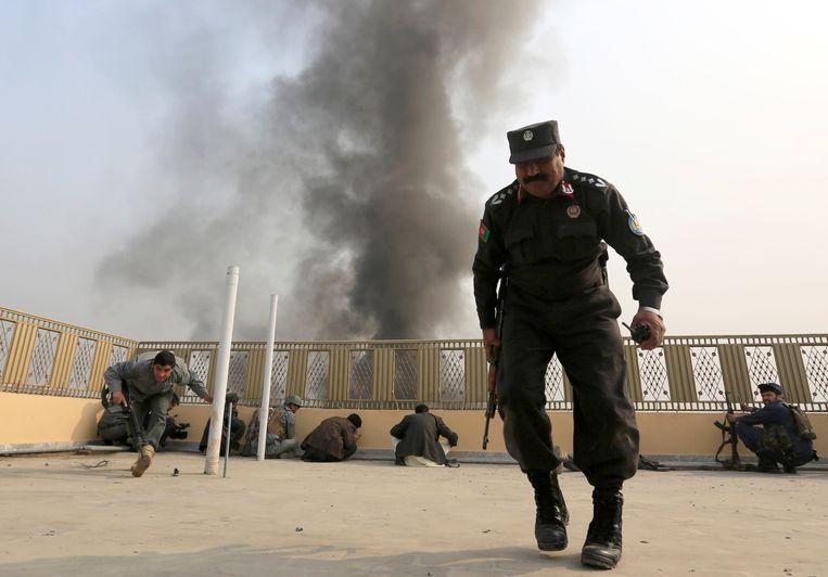 Afghaanse politie-agenten zoeken dekking na de aanval op het kantoor van Save The Children.