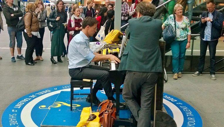 Premier Mark Rutte, die overwoog het conservatorium te doen, kroop op 16 juni achter een piano op Den Haag CS. Beeld Peter Visser