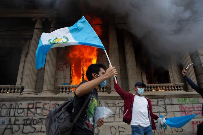 Demonstranten met de nationale vlag van Guatemala voor het brandende parlementsgebouw.