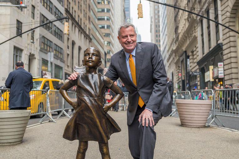 De burgemeester van New York, Bill de Blasio, besloot maandag dat het beeldje van 'fearless girl' in elk geval nog een jaar mag blijven staan tegenover de beroemde 'charging bull' nabij Wall Street in het zakendistrict van zijn stad. Beeld Photo News