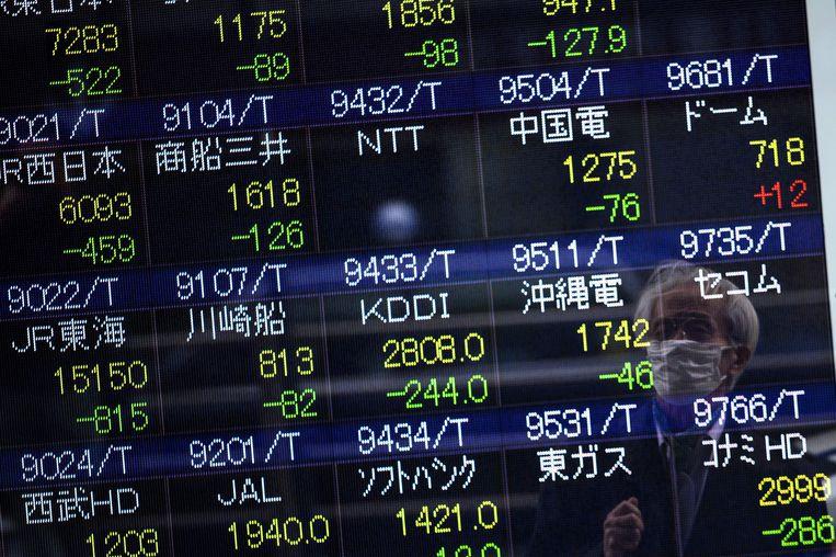 Een man bekijkt de cijfers van de beurs in Tokio. Beeld AFP