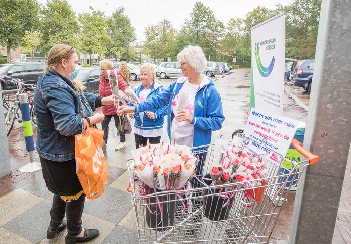 Omdat het de week van de eenzaamheid is delen Liliane Schoone en Tony Pekaar van de Seniorenraad rozen uit. Lianne Essaber geeft de roos aan haar buurvrouw.