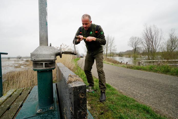 Twan Teunissen maakt de sluis dicht waardoor er geen water meer terug kan stromen van de Oude Waal naar de Waal.