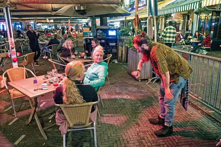 Een medewerker van een café waarschuwt klanten dat ze om tien uur sluiten. Beeld Guus Dubbelman/de Volkskrant