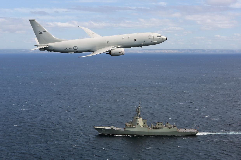 Een vliegtuig van de Australische luchtmacht vliegt over een luchtverdedigingsschip van de marine.