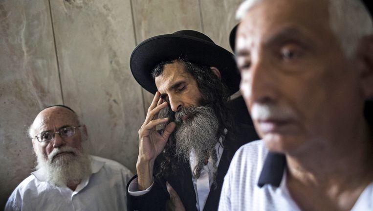 Joodse mannen tijdens de begrafenis van Emanuel en Miriam Riva, die bij de aanslag omkwamen. Beeld getty