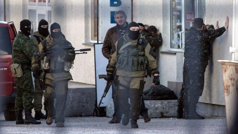 Russische soldaten arresteren Oekraïense officiers tijdens een operatie in Simferopol vandaag. Beeld afp