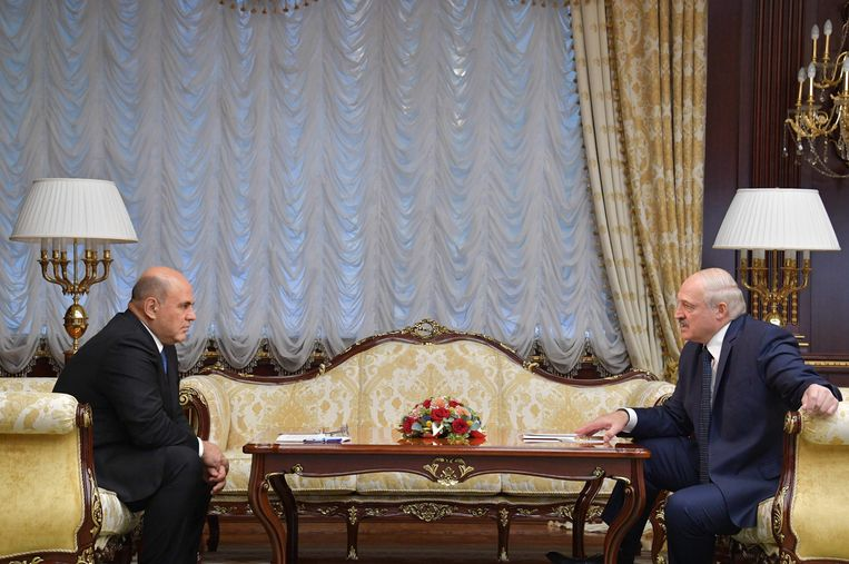Russisch premier Mikhail Mishustin spreekt met de Belarussische president Aleksandr Loekasjenko tijdens een ontmoeting in Minsk.  Beeld AFP