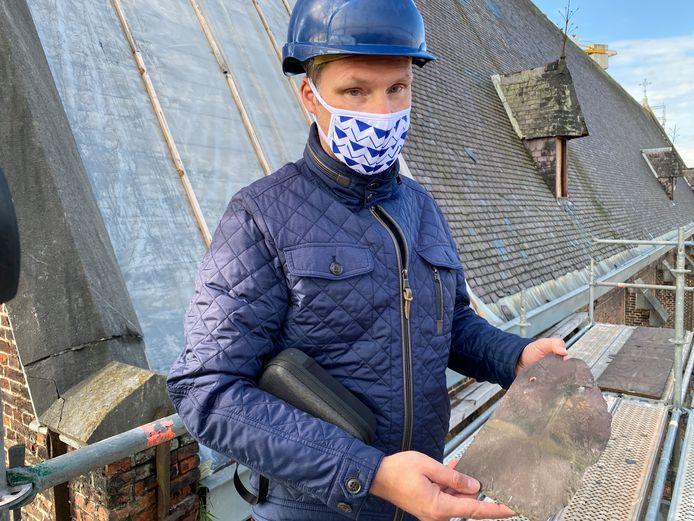 Claude Nijs toont een leisteen van het dak