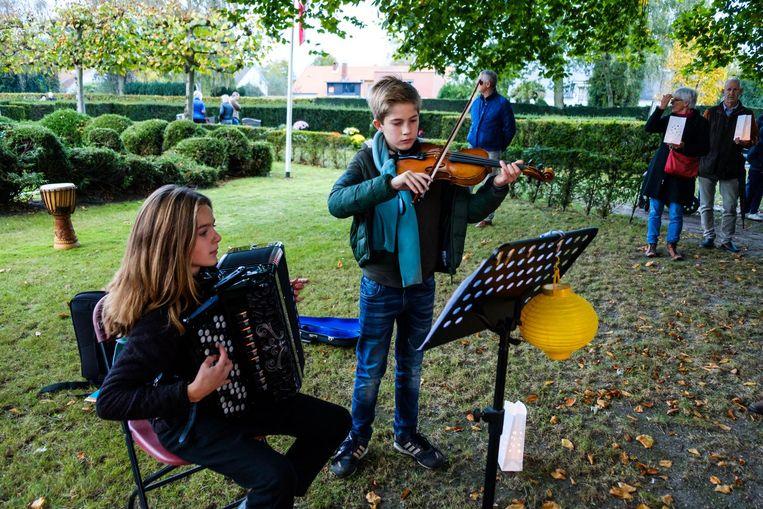 Twee jonge muzikanten brengen ingetogen muziek op de begraafplaats.