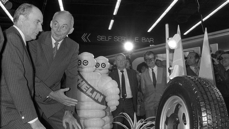 François Michelin (rechts) toont toenmalig president Mitterand op een autoshow in 1984 de nieuwste band van zijn bedrijf. Beeld null