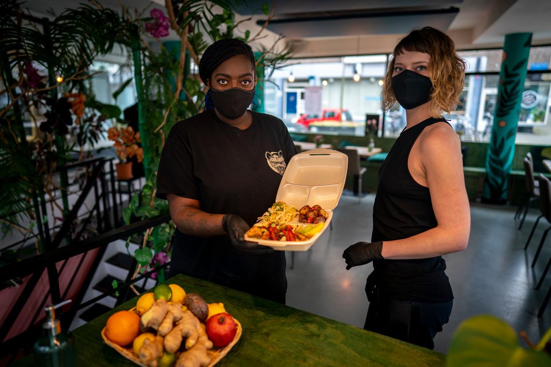 Manuela Goncalves Tavares in haar CaribischerestaurantCoco. Rechts kok Manouk Schouwenburg, die voor het personeel mondkapjes naait.