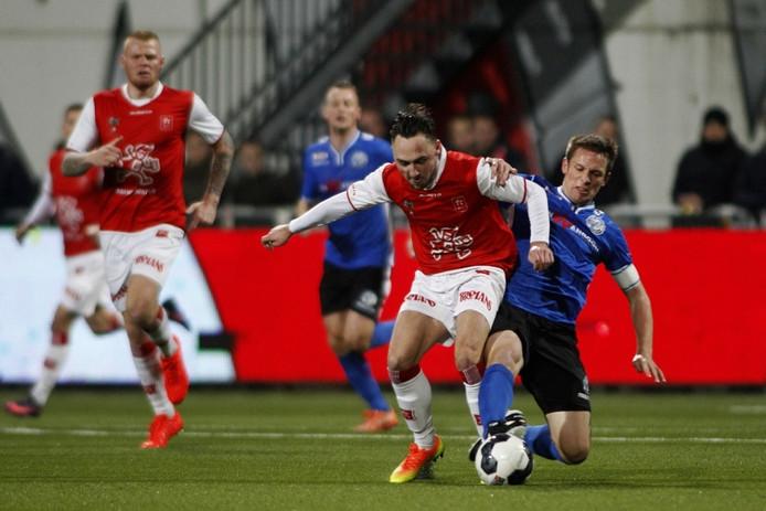 FC Den Bosch-aanvoerder Bart Biemans is hier met een sliding op de bal MVV-goalgetter Joeri Schroijen nog de baas.