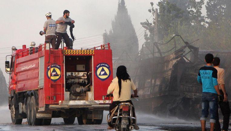 Hulpverleners blussen de trucks. Beeld afp