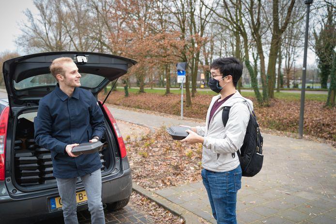 Job Brom reikt een pakketje uit aan een internationale student die vanwege corona met kerst in Wageningen moet blijven.
