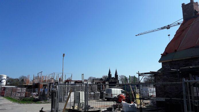 De nieuwe wijk Westwaard in aanbouw met op de achtergrond de twee torens van de kerk HH Martelaren van Gorkum aan de Erasstraat.