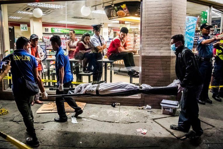 Edwin Mendoza Alon-Alon (36), in het hoofd geschoten, wordt weggedragen. Beeld null