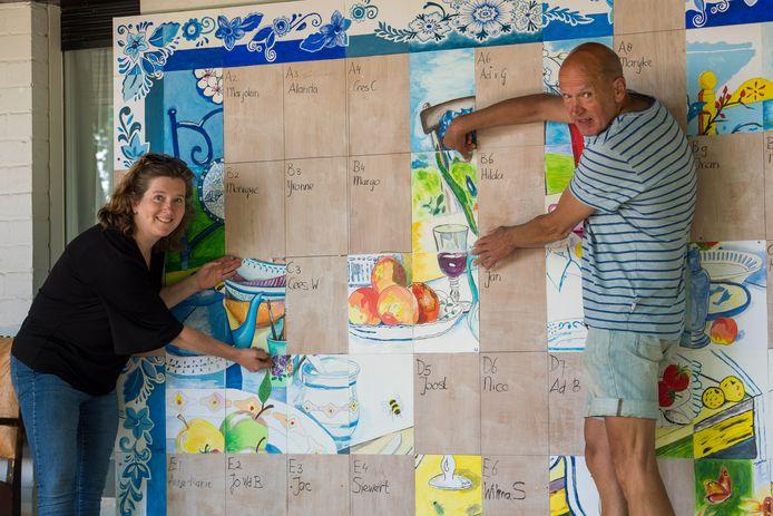 Jelske Loots (links) en Jak Janssen voegen hun deel bij het kunstwerkvan zorgatelier Buiten.