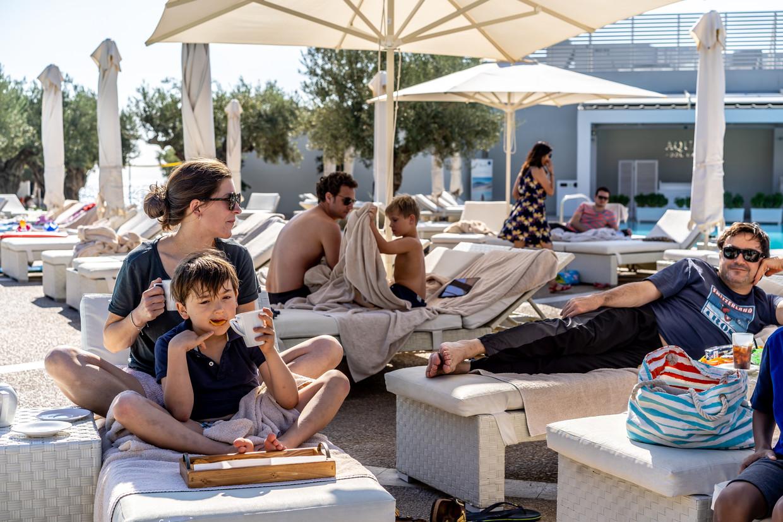 Gasten van het Ikos Olivia Resort aan het zwembad. De koffie komt van een barista. Beeld null