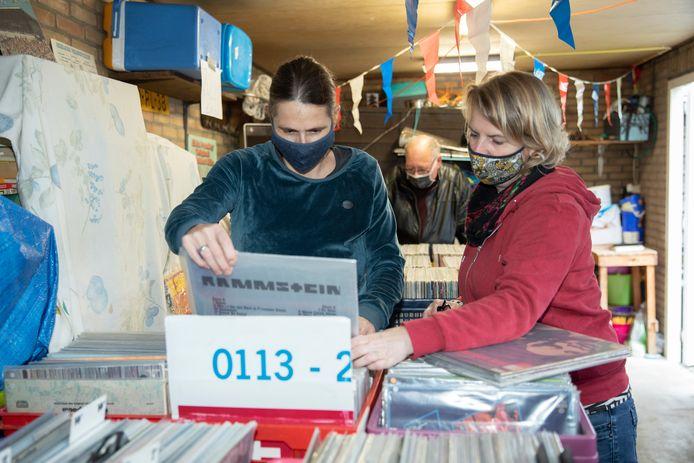 Jeanine van der Horst (blauw mondkapje) en Mariska Ringelberg (geel mondkapje) vonden enkele LP's van hun gading van ABBA tot Iggy Pop en Tom Waits.