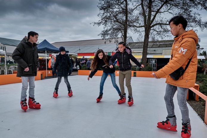 Schaatsen op de plastic ijsbaan op de wintermarkt.