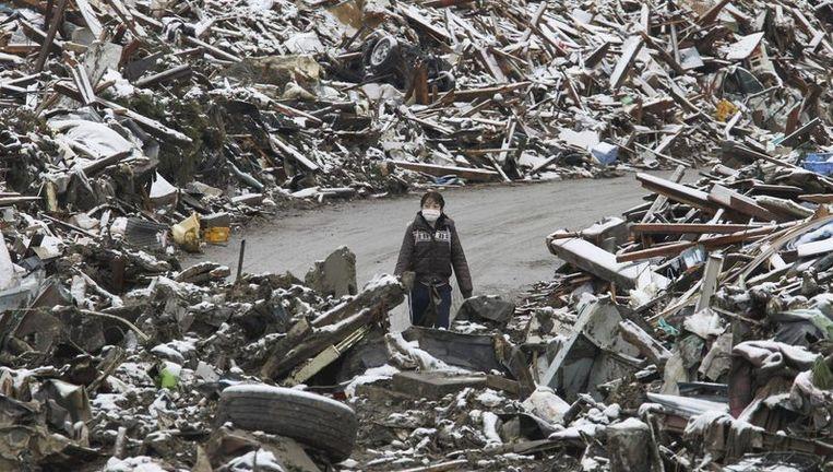 Een vrouw doorzoekt de restanten van het getroffen stadje Minamisariku. Beeld reuters
