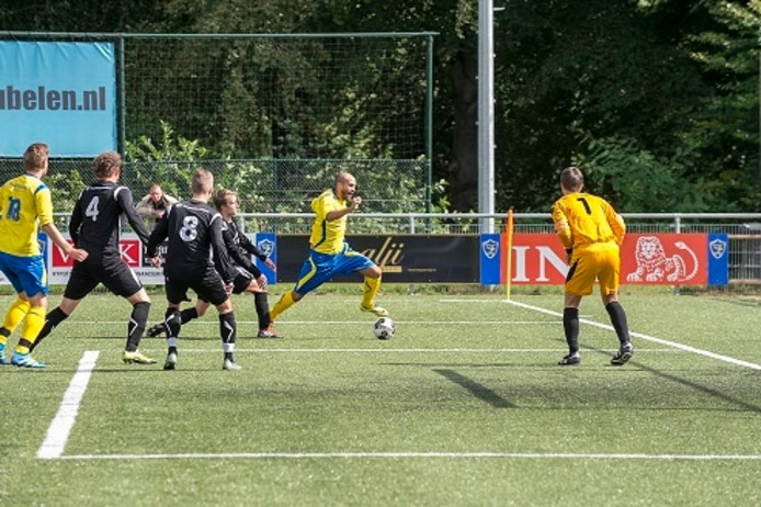 SC Veluwezoom-spits Nathan Heljanan (m) gaat over de voet, waarna de bal op de stip gaat.