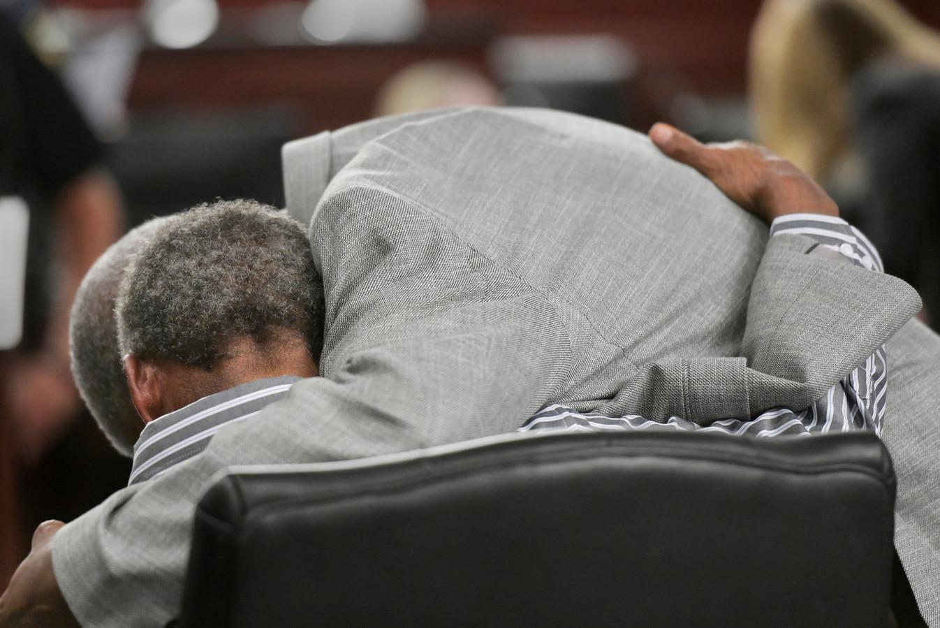 Clifford Williams (76) krijgt een knuffel van zijn neef Hubert Myers (61) na het nieuws in de rechtbank.