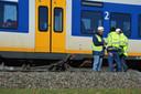 Medewerkers van ProRail overleggen terwijl mensen in de trein zitten. Op de voorgrond een brokstuk