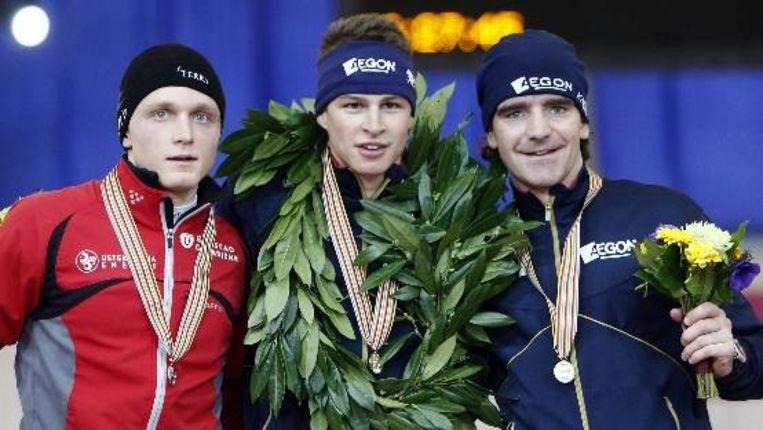 Sven Kramer temidden van Havard Bokko (L) en Bob de Jong (R) tijdens de podiumceremonie van de 10.000 meter zaterdag tijdens de wereldkampioenschappen afstanden in Vancouver op de Richmond Olympic Oval. (ANP) Beeld