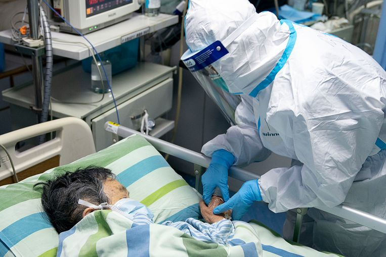 Een hulpverlener in het Zhongnan universitair ziekenhuis van de Chinese stad Wuhan, waar het virus zou zijn uitgebroken, bij een van de patiënten. Het medisch personeel is volledig ingepakt in beschermende kledij.