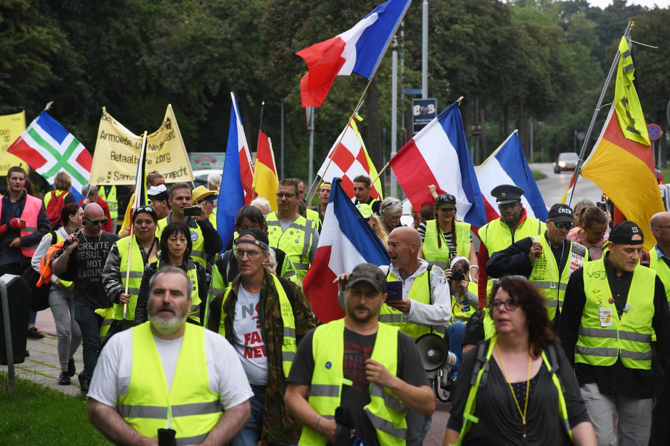 Gele hesjes met Nederlands, Duitse, Franse en Groningse vlaggen in Tiel.