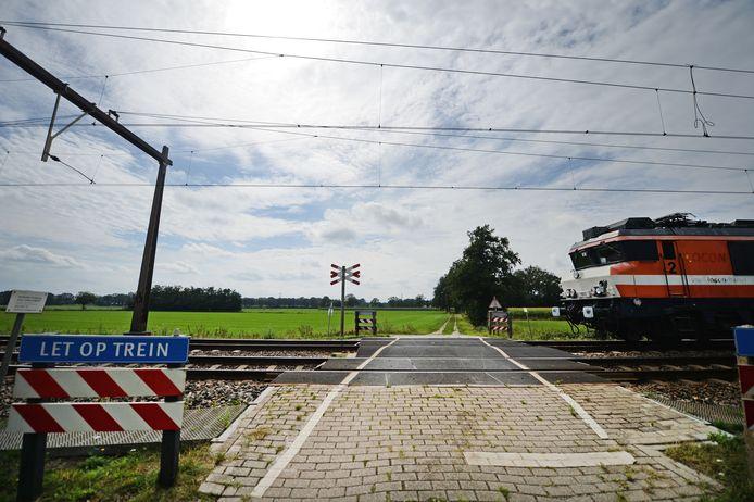 De onbewaakte spoorwegovergang aan Het Vlier. Volgens drie opties komt hier een spoortunnel en loopt de nieuwe rondweg door het essenlandschap aan de overzijde.