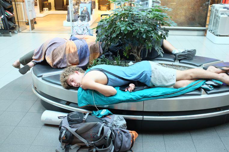 Gestrande reizigers op Schiphol. Voor de gehele luchthaven werden gisteren 300 vertrekkende en aankomende vluchten geannuleerd.