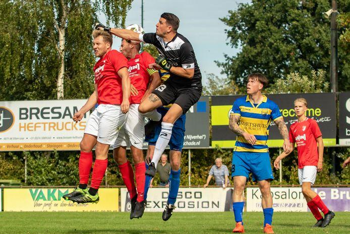 Rood-Wit-spelers Edwin Jaspers en Boy van Steen gaan het kopduel aan met FC Boshuizen-doelman Dennis Hendriks.