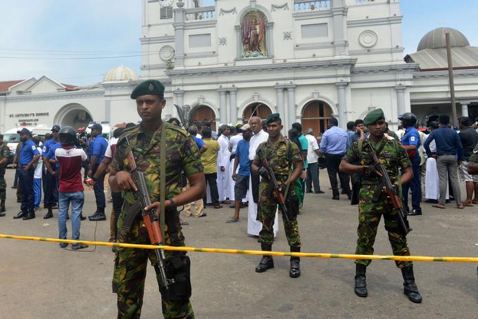 Veiligheidspersoneel houdt de wacht buiten het kerkgebouw na een explosie in de St. Anthony's Shrine in Kochchikade.