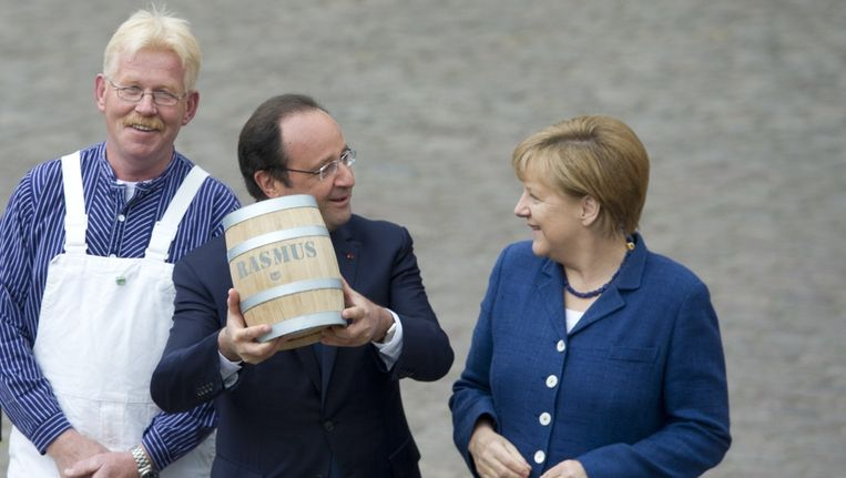 President Hollande poseert met het vat haringen dat hij van Merkel cadeau heeft gekregen.