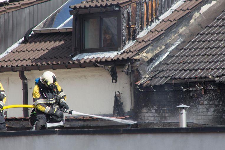 Een brandweerman blust de brand die begon in een slaapkamer aan de achterzijde van de woning.