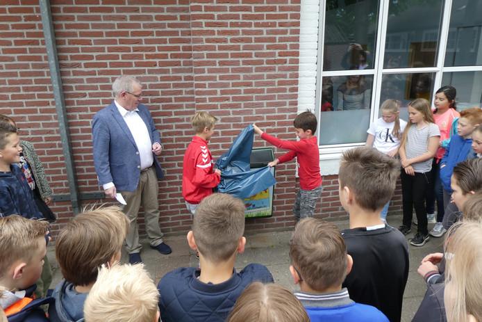 Tijn en Lars halen het plastic weg, zodat ook hun winnende tekening zichtbaar wordt.